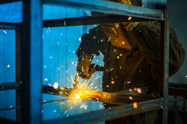 Worker in overalls and protective mask welds metal