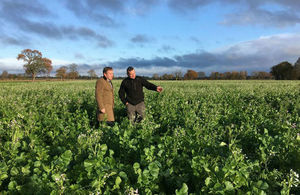 George Eustice with farmer in field