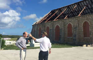 Two men in conversation in front of a storm-damaged church