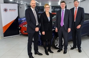 Greg Clark and representatives from the automotive sector standing in front of a car.