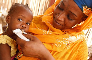 Woman feeding child in the Sahel