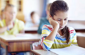 young pupil looking sad in classroom