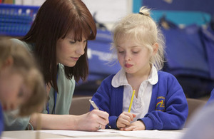 Teacher helping pupil with writing