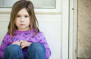 young girl sat outside her front door