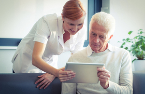 Nurse showing patient health data on tablet.
