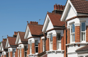 Row of houses with blue sky to illustrate UK house price index