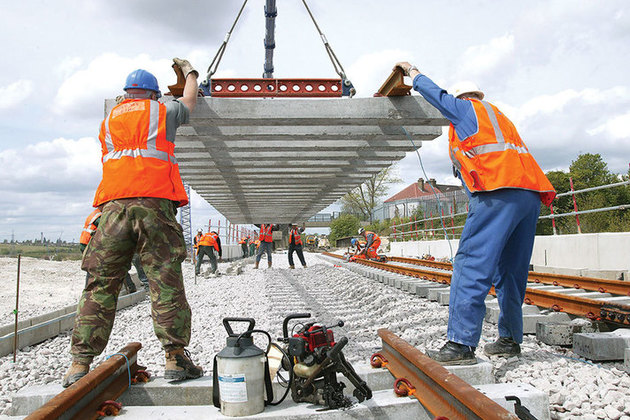 Image of rail workers with rail tracks.