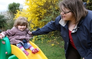 Young girl on playground slide with carer