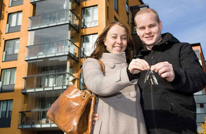 A young couple hold the keys to their newly purchased home