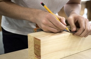 Young person's arm measuring a wooden block