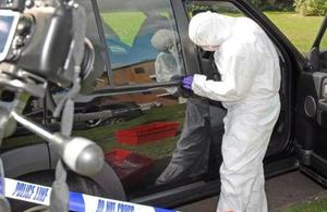 Forensic expert at crime scene. Crown copyright