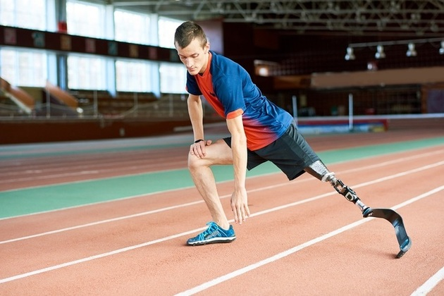 Boy on running track with prosthetic leg