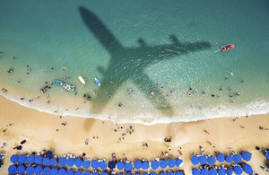 Image of a beach with the shadow of a plane flying overhead.
