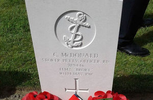 Wreaths adorn the newly marked headstone for PO McDonald, Crown Copyright, All rights reserved