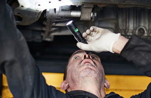 MOT tester carrying out a test under a car