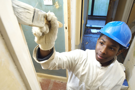 Young people living independently report: image shows a young man painting and decorating.