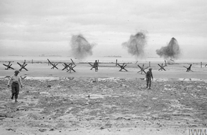 Royal Navy personnel from an obstacle clearance unit blowing up German beach obstacles at La Riviere, Normandy, 9 June 1944. Image credit: © IWM (A 23993)