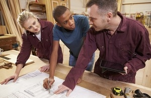 carpenter with apprentices in workshop