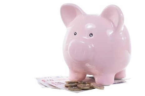 Pink piggy bank with coins and notes at its feet