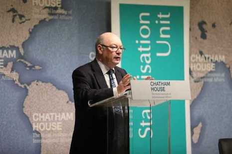 Minister for International Development Alastair Burt stands at a lectern with a map of the world behind him.