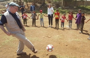 Minister Burt playing football with refugee kids in the Bekaa