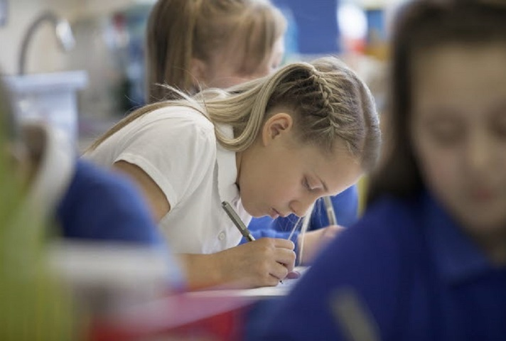 Female pupil writing.