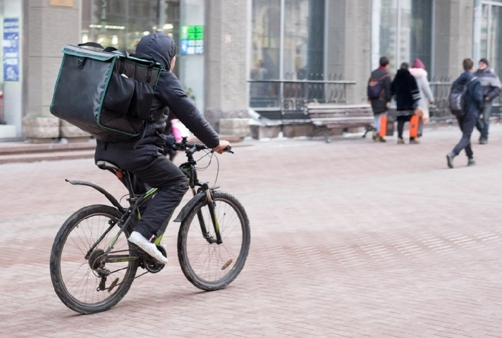 Man on bike with food delivery bag in his back