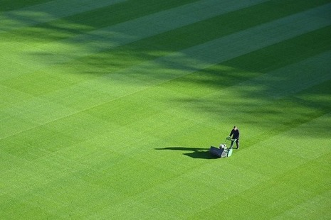 Groundsman mowing the grass of a sports field.