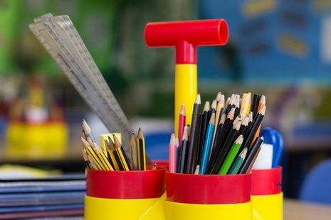 Pencils and pens in colourful holder.