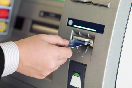 A man inserting his bank card into an ATM machine.