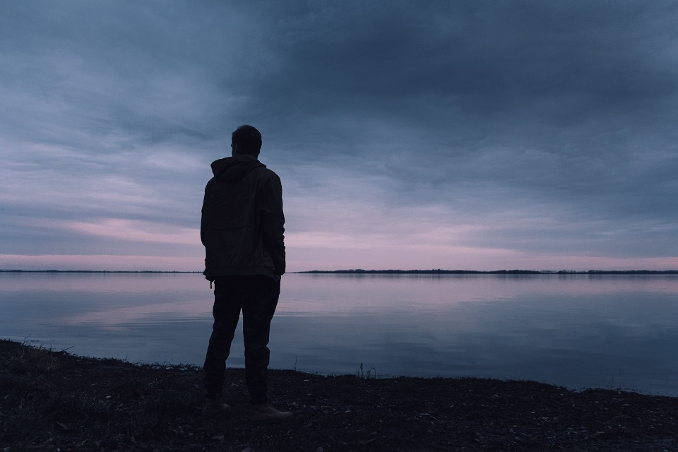 Silhouette of man standing at lake