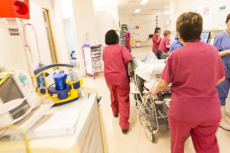 Nurses wheeling a patient through a ward.
