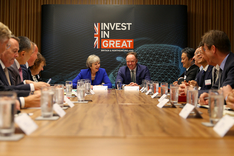 "Prime Minister Theresa May at the head of the Automotive Investment Roundtable with ""Invest In GREAT"" banner in the background"