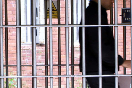 Prison officer locking a gate