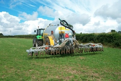 Tractor towing slurry injector in field