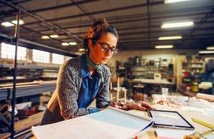 An engineer reviews plans in her workshop