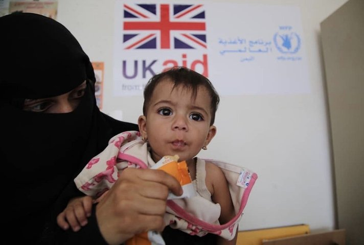 A malnourished child receives therapeutic food at a UK-supported clinic in Yemen.