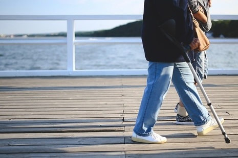 Woman using crutches while walking along pier