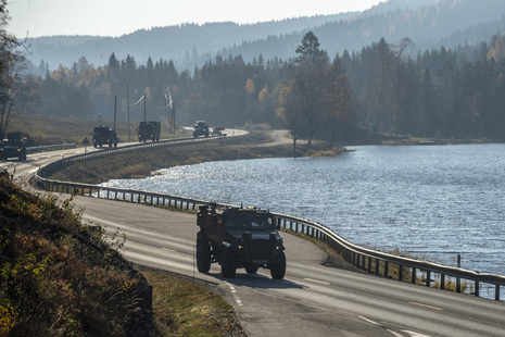 A Foxhound patrol vehicle leads a convoy of British Army trucks along winding road by the side of a Norwegian lake