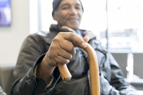 An elderly man with a walking stick, smiling.