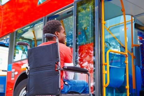 A wheelchair user boards a bus