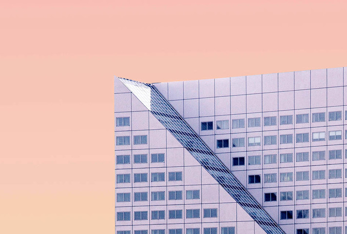 Sloped roof of a skyscraper set against a pink sky