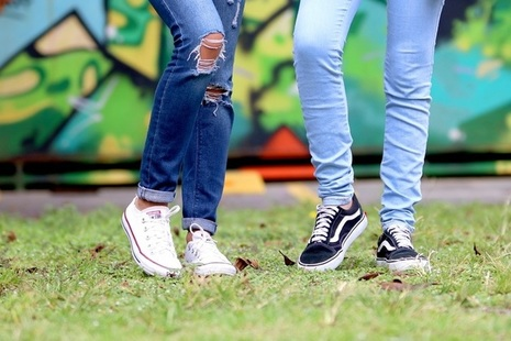 Two teenagers, seen from the legs down, standing on grass