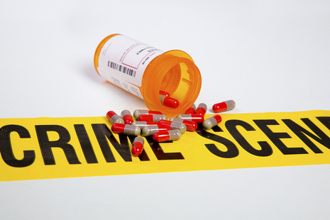 pills spilling out a bottle with crime scene tape