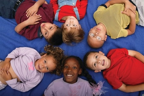 6 children lying in a circle, heads touching, on a blue background