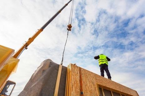 Construction worker guides a crane lifting a modular structure