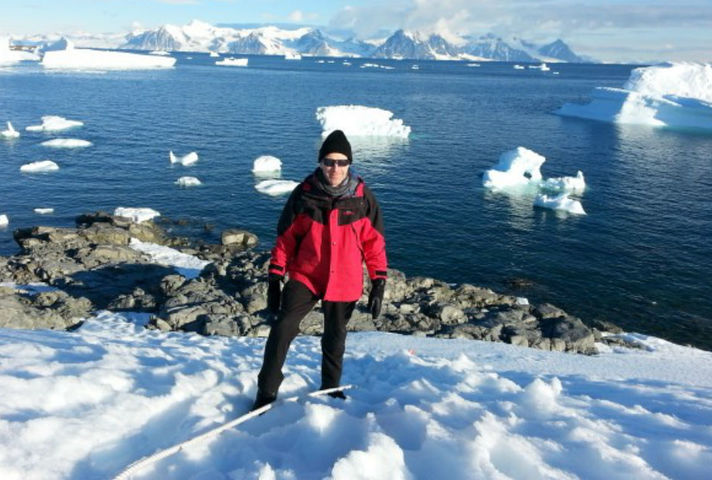 Ben Merrick pictured in Antarctica, dressed in cold-weather gear and with the sea and icebergs in the background.