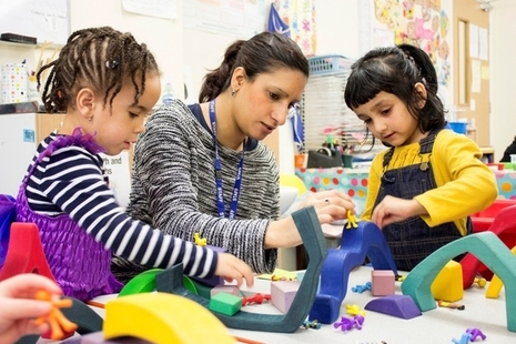 Childcare professional with 2 young girls playing at a crafts table