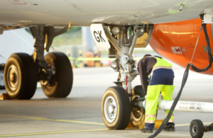 Support services working on an airplane on the runway.