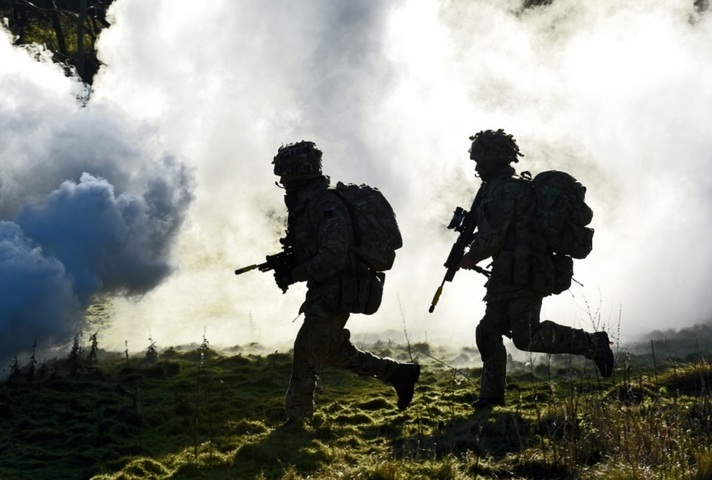 Two soldier silhouettes running through smoke